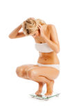 Sports Woman Crouching on Bathroom Scales. Royalty Free Stock Photography
