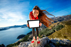 Sports woman with digital tablet on the mountain royalty free stock photography