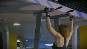 A sports woman does pulling the whole body on the crossbeams in the sports club. A sporty woman with stretchable gloves makes the whole body pull up on the bars stock video footage