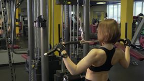 Sports woman doing physical exercises on Hammer`s Training apparatus. A sportswoman who came to a fitness club performs physical exercises on the Hummer stock video footage