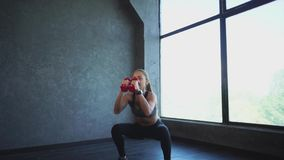 A sports woman doing sit-ups and jumping, she is holding dumbbells stock footage