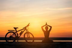 Sports woman doing yoga at sunrise on the sea beach against the background of orange sky and bicycle. Fitness concept. Royalty Free Stock Image