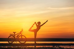 Sports woman doing yoga at sunrise on the sea beach against the background of orange sky and bicycle. Fitness concept. Royalty Free Stock Photos