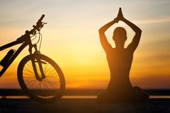 Sports woman doing yoga at sunrise on the sea beach against the background of orange sky and bicycle. Fitness concept. Royalty Free Stock Images