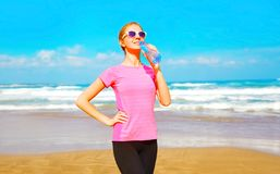 Sports woman drinks water from bottle on the beach near the sea. On a summer day Royalty Free Stock Images