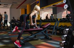 A sports woman is engaged in a gym with metal dumbbells on the bench for bench press. An attractive sports woman, with blond hair, European appearance, athletic Stock Image
