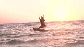 A girl in a diving suit is engaged in kitesurfing at dawn, slow motion. Sports woman is engaged in kitesurfing at dawn, summer vacation at sea stock video footage