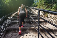 Sports woman going up on stone stairs Stock Image