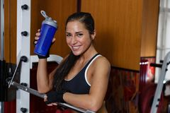 Sports woman in the gym. The sports young woman with a protein cocktail in a shaker stands in a gym. Sports nutrition stock photos