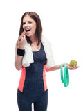 Sports woman holding apple and eating chocolate Royalty Free Stock Photo