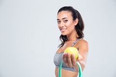 Sports woman holding apple and measuring type Stock Photography