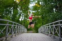 Sports woman jumping on wooden bridge Stock Photography