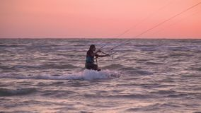 Sports woman kitesurfing on the sea at dawn. Girl on the sea on a windy day, a girl in a suit for diving is engaged in kitesurfing stock footage
