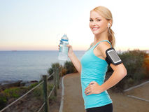 Sports woman listening to music and drinking water Stock Image