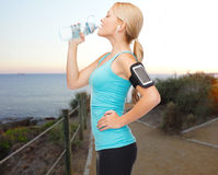 Sports woman listening to music and drinking water Stock Photography