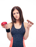Sports woman making choice between apple and chocolate Royalty Free Stock Photography