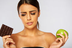 Sports woman making choice between healthy apple Royalty Free Stock Image