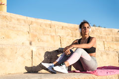 Sports woman outdoor in a stairs doing exercise listening music. Sports woman outdoor in a stairs resting  after doing exercise listening music Royalty Free Stock Photography