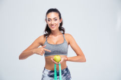 Sports woman pointing finger on apple and measuring type is Stock Photo