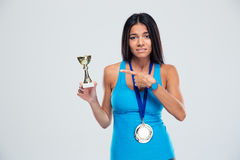 Sports woman pointing finger on the winners cup Royalty Free Stock Image