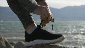 Sports woman getting ready for run tying laces of running shoes on the beach. Sports woman runner getting ready for run tying laces of running shoes on the beach stock video