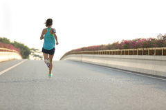 Sports woman runner running on city road Stock Photography