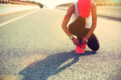 Sports woman runner tying shoelace on city road Stock Images