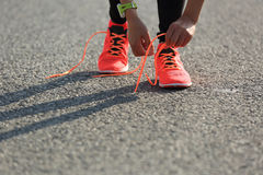 Sports woman runner tying shoelace on city road Royalty Free Stock Image