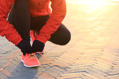 Sports woman runner tying shoelace on city road Stock Photos