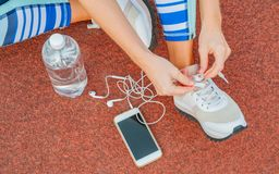 Sports woman runner tying shoelaces. Woman lacing her sneakers on a stadium running track. Workout concept royalty free stock photos