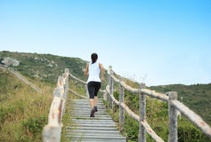 Sports woman running on mountain stairs Stock Photography