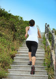 Sports woman running on mountain stairs Stock Photos