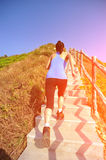 Sports woman running on mountain stairs Royalty Free Stock Images
