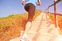 Sports woman running on mountain stairs Royalty Free Stock Image