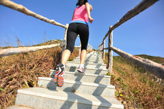 Sports woman running at mountain stairs Royalty Free Stock Image