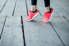 Standing in running shoes. Sports woman in running shoes standing on toes on the wooden floor, close-up view focused on the sneakers royalty free stock photography