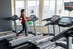 Sports woman is running on the treadmill Stock Image