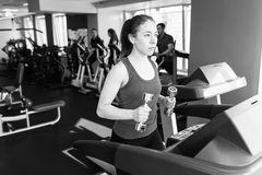 Sports woman is running on the treadmill Stock Images