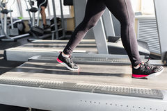 Sports woman is running on the treadmill Royalty Free Stock Image