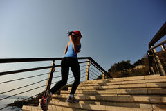 Sports woman running up on stone stairs Royalty Free Stock Photo