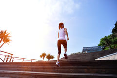 Sports woman running up on wooden stairs Royalty Free Stock Photos