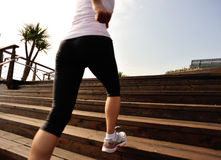 Sports woman running up on wooden stairs Stock Photo