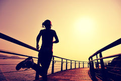Sports woman running on wooden boardwalk Royalty Free Stock Image