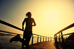 Sports woman running on wooden boardwalk sunrise seaside Royalty Free Stock Photography