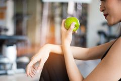 Sports woman sitting and eating green apple in fitness training gym. Food and Fruit and nutrition concept. Relax and Clean food. Concept. Healthcare and workout royalty free stock photography