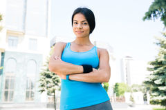 Sports woman standing with arms folded outdoors Stock Images