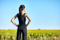 Sports woman standing in field and admiring nature Stock Photos
