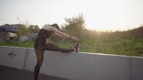 Sports woman stretches leg, putting her foot on a concrete fence. Sporty woman stretch legs by placing her foot on the fence, girl doing running warm up before stock footage