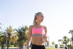 Sports woman taking break after training with copy space sky background Royalty Free Stock Image