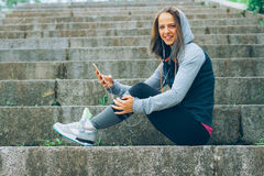 Sports woman and technology. Smiling Athlete with phone relaxing on stairs in the park after workout Stock Photos